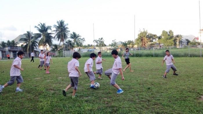Các em học sinh đá bóng tại sân bóng Trường